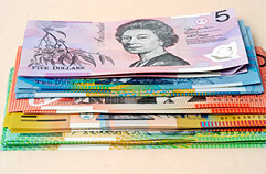 Stack of banknotes with the $5 banknote on top.