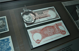Collectible banknotes displayed in a cabinet, with a magnifying glass /